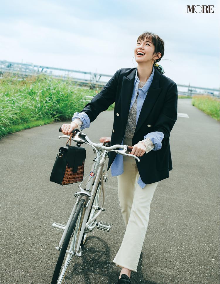 レーストップスとシャツにネイビージャケットをはおり、ホワイトデニムをはいて自転車を押す佐藤栞里