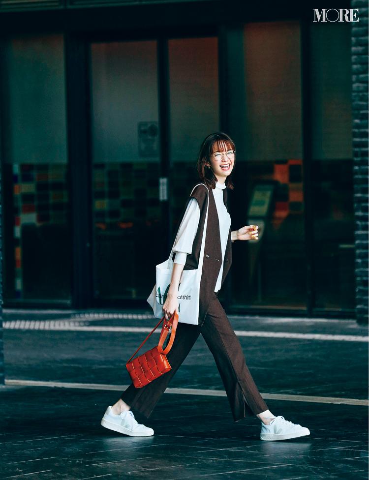 セットアップを着て白スニーカーをはいた、メガネをかけた佐藤栞里