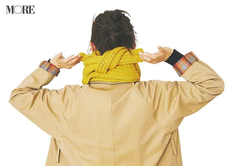 首の後ろでマフラーを結ぶ女性