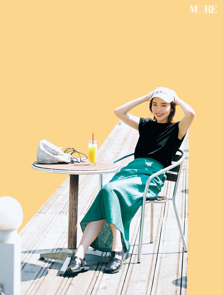 黒トップス×グリーンのスカートコーデに白キャップをかぶった飯豊まりえ