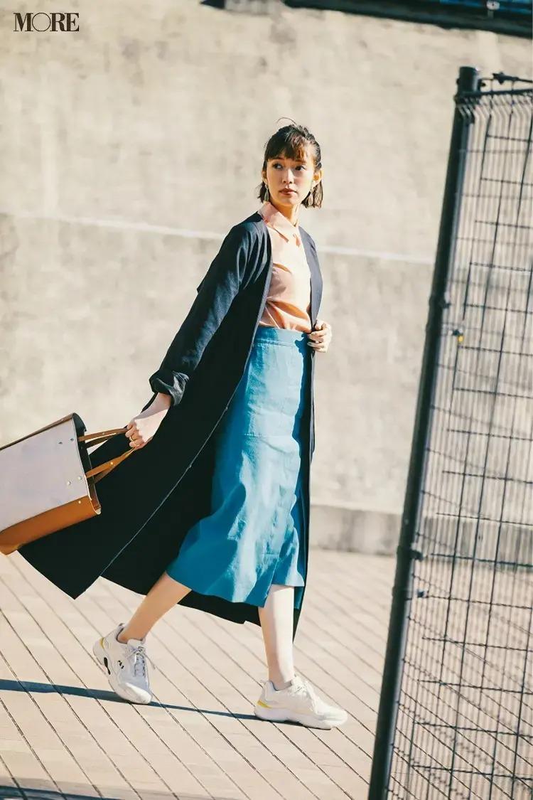 【春のスニーカーコーデ】ダーク色コート×暖色系のシャツ×ブルーのスカート×白スニーカー