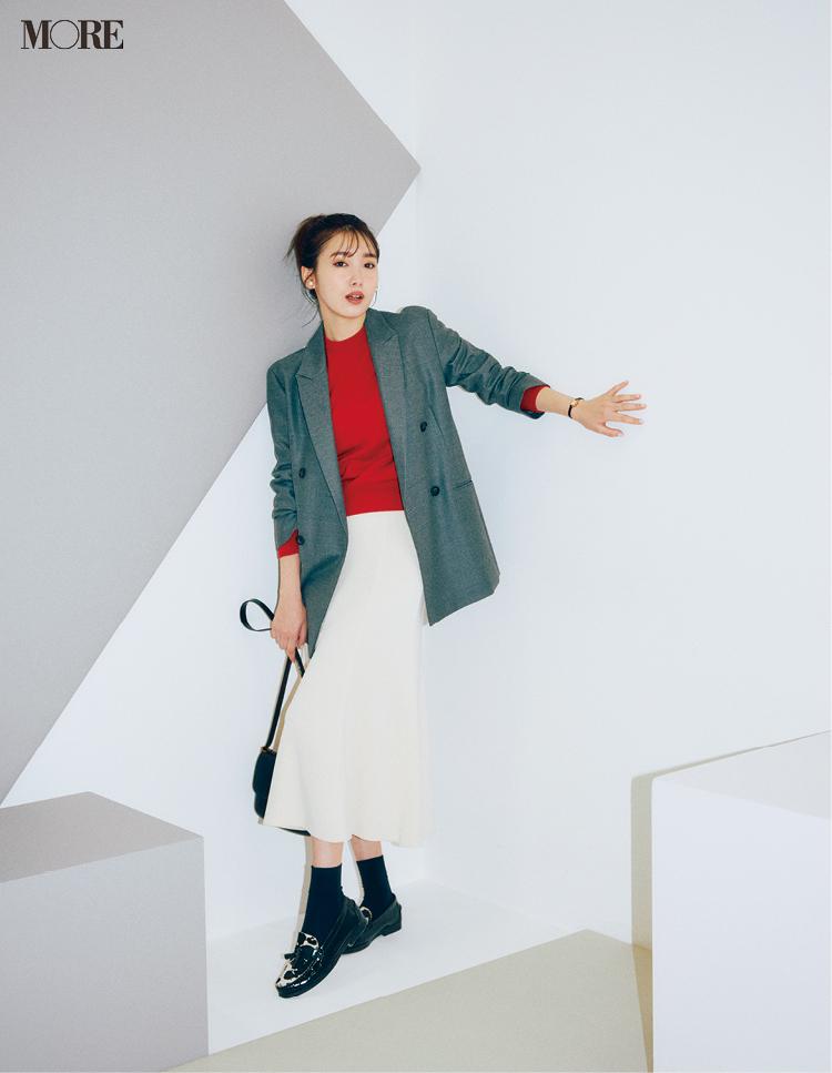 赤ニットにグレージャケットをはおり、白スカートをはいた飯豊まりえ