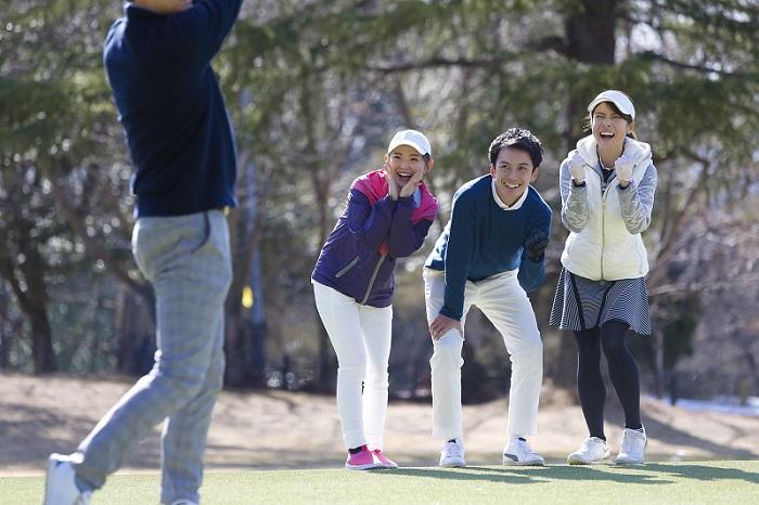 ゴルフ場で打つ人を応援しているシーン