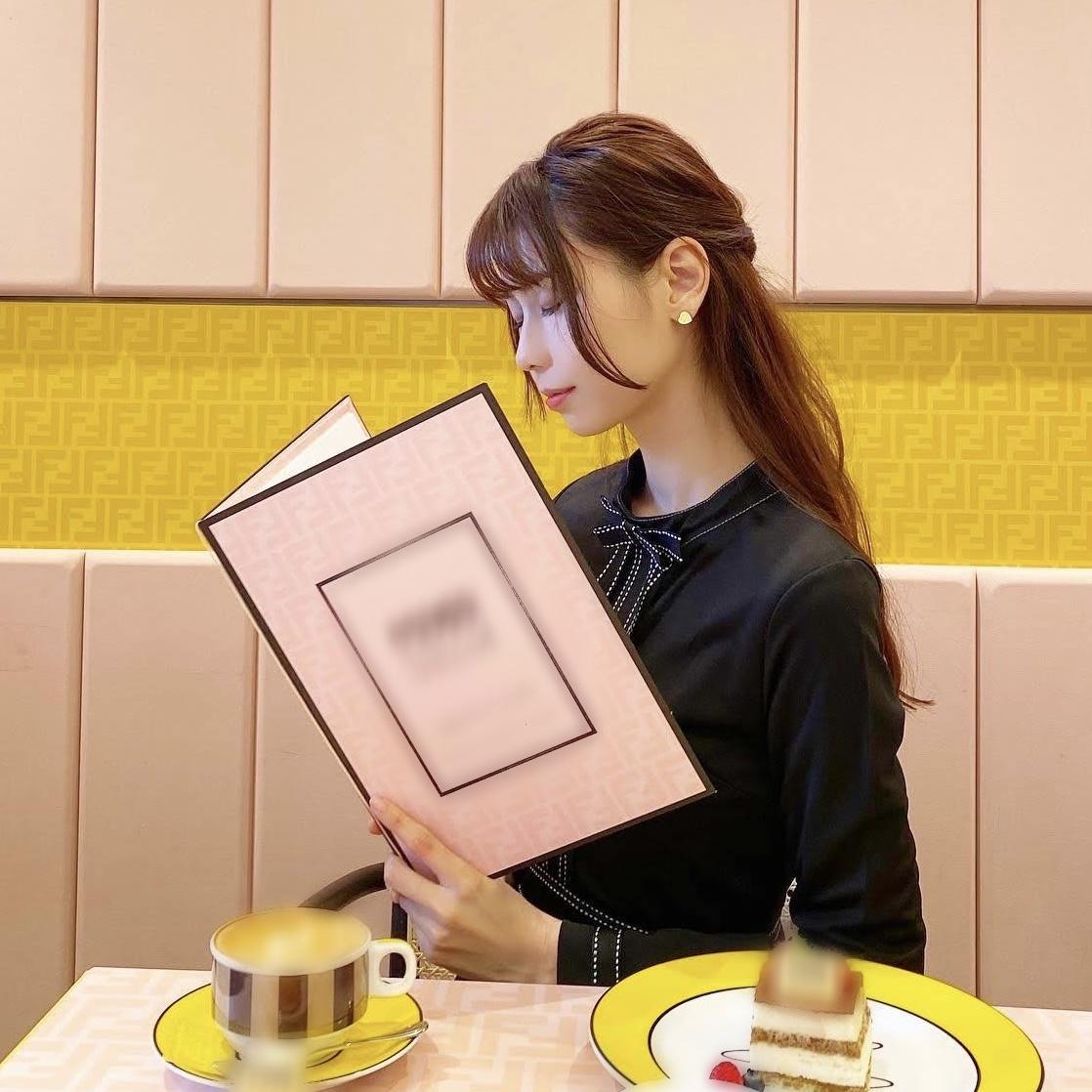 カフェでピンク色のメニューを見ている目を閉じた女性