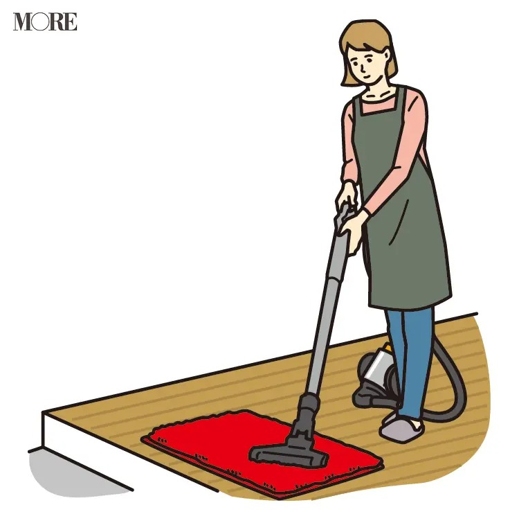 風水の開運掃除法で玄関マットに掃除機をかける女性