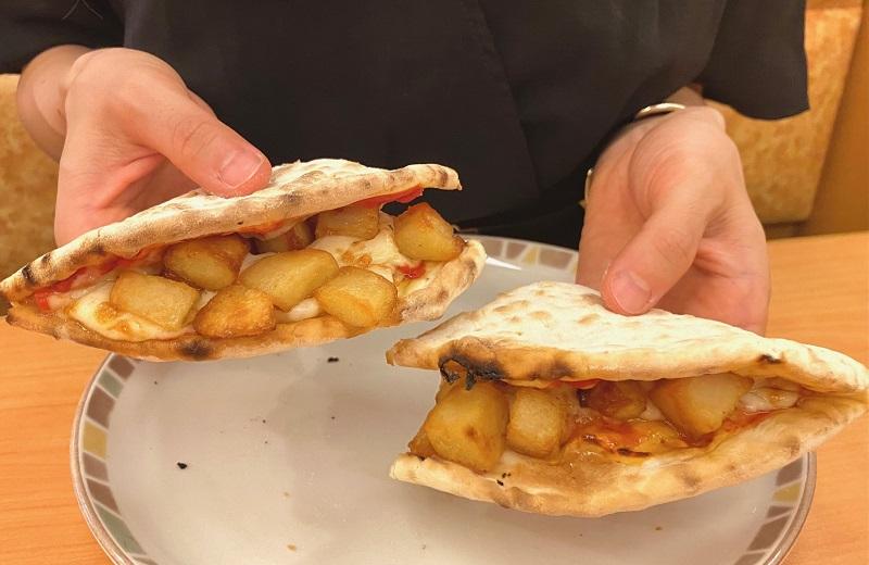 イタリア人がすすめる「サイゼリヤのおいしい食べ方」カルツォーネを持っている様子