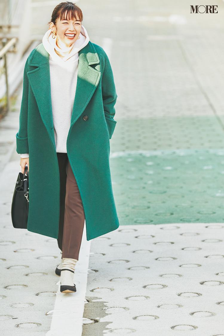 グリーンのコートをパーカーにはおった佐藤栞里