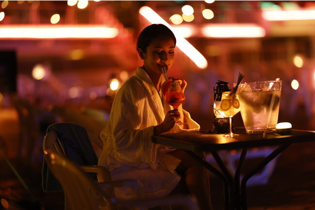 「NAKED NIGHT SAUNA HOTEL NEW OTANI -CITY RETREAT-」の夜の部で、プールサイドにてドリンクを飲んでいる女性