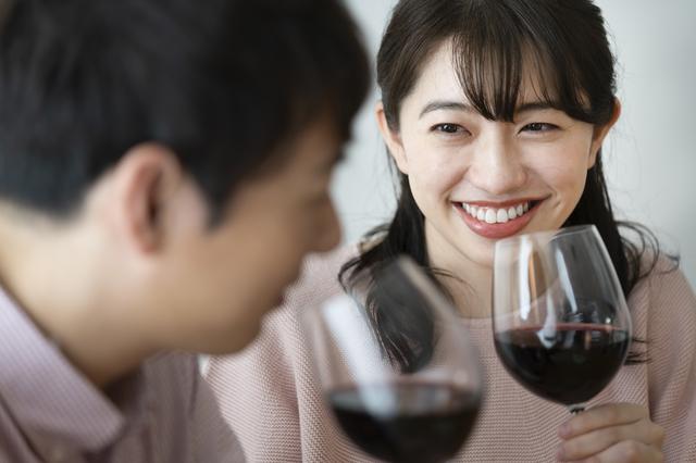 男性とデート中、ワイングラスを手に持っている女性