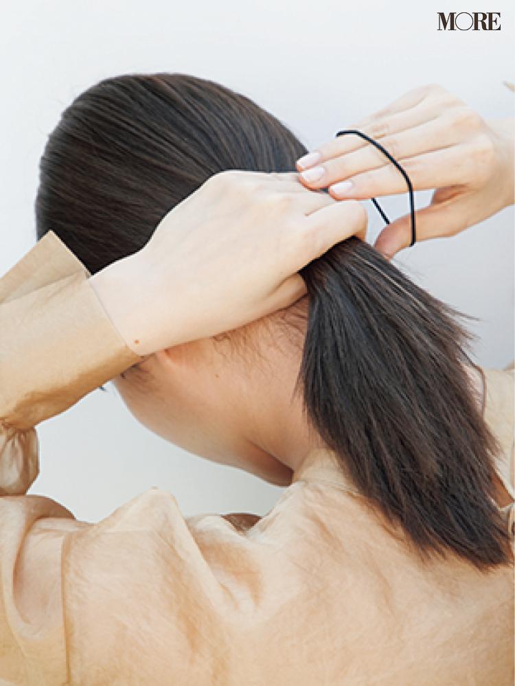 梅雨のポーニーテールヘアアレンジで髪を結ぶ女性