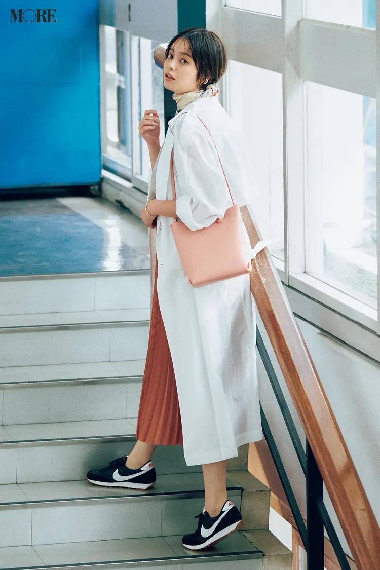 白シャツ×オレンジプリーツスカートにナイキのスニーカーをはいた岸本セシル