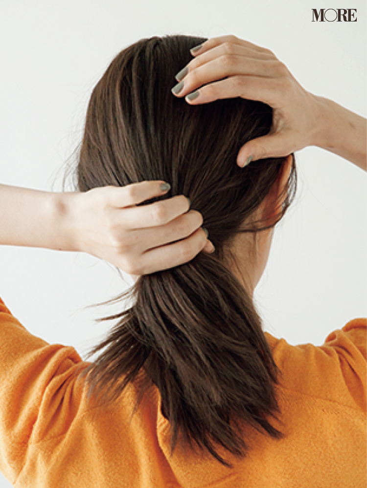梅雨の低めおだんごヘアアレンジで髪にワックスをつける女性