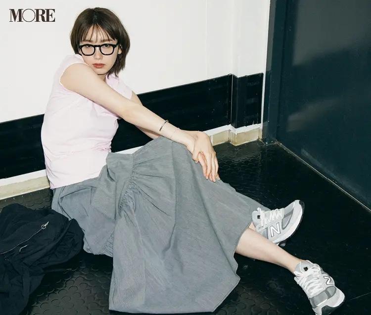 ピンクのTシャツ×グレーのスカートコーデでメガネをかけた飯豊まりえ